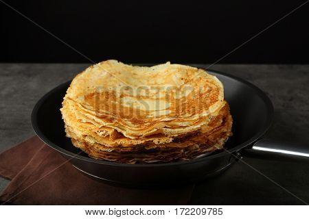 Pile of tasty pancakes in frying pan
