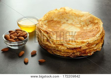 Plate with delicious pancakes, almonds and honey on table