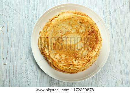 Plate with tasty pancakes on white wooden table