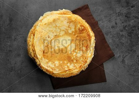 Stack of delicious pancakes on grey table