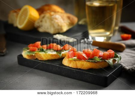 Delicious toasts with tomatoes and creamy cheese on wooden board
