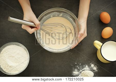 Female hands making dough in glass bowl on table, top view