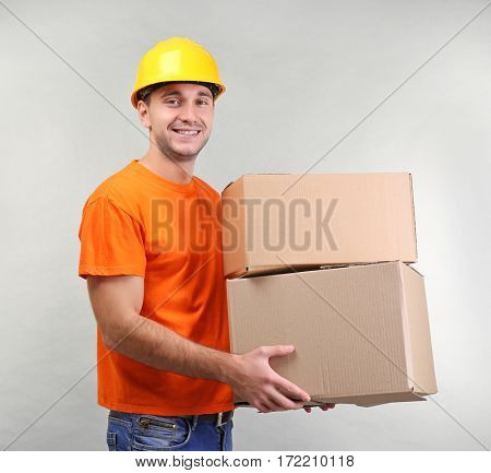 Handsome warehouse worker with cardboard boxes on light background