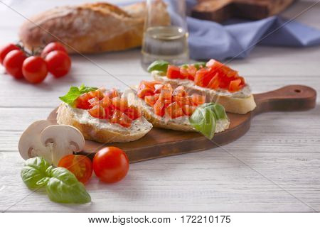 Delicious bruschetta with chopped tomatoes on wooden board