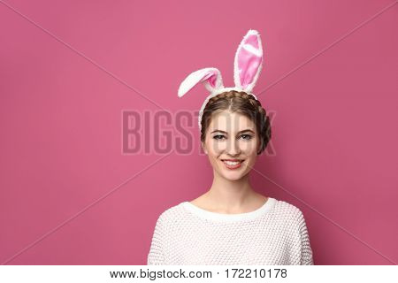 Beautiful young woman with bunny ears on color background