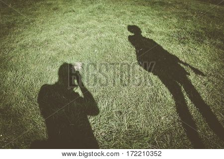 Shadow of photographer taking photo of tourist with dog on lead