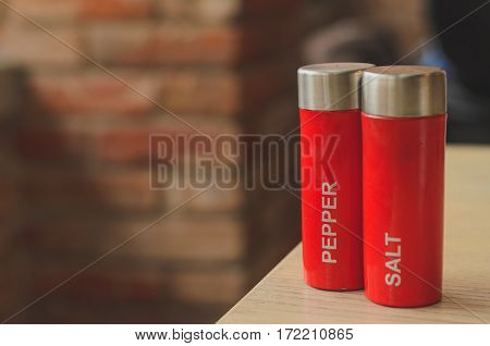 Red plastic salt cellar and pepperbox on a wooden table on loft brickwall background faded colors