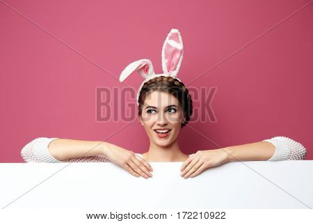 Beautiful young woman with bunny ears and blank poster on color background