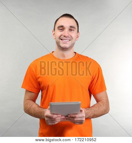 Handsome man with tablet computer on light background