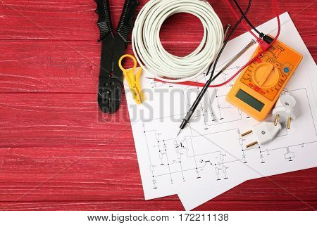 Electrician tools and schemes on red wooden background