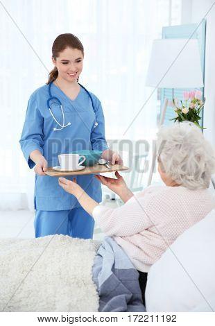 Nurse giving breakfast to elderly woman