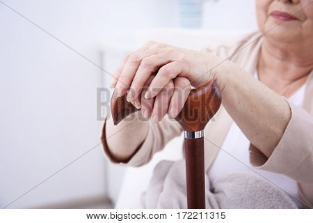 Female hands holding walking stick closeup