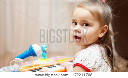 Little adorable girl playing with a toy piano at home