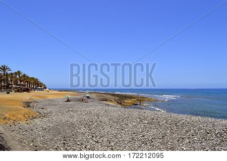 Playa De Las Americas beach Tenerife Canary Islands Spain Europe - June 12 2016: Pebble beach in Playa de las Americas Tenerife