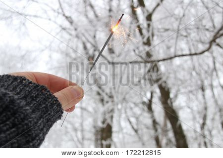 Man holding a burning sparkler firework in his hand.
