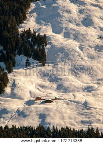 Evening view of alpine hut in the steep slope. Winter backountry ski touring area, Austrian Alps, Europe.