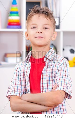 Half-length emotional portrait of caucasian boy. Funny teenager with arms folded at room. Handsome child looking at camera.