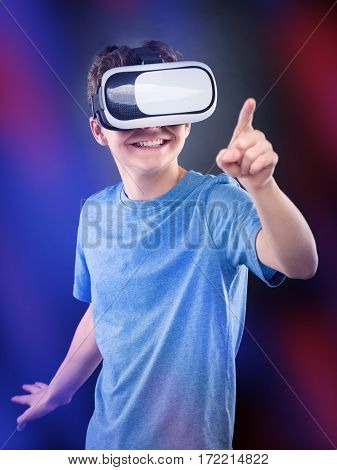 Happy teen boy wearing virtual reality goggles playing video games, on colorful bokeh background. Cheerful smiling looking in VR glasses and gesturing with his hand. Child experiencing 3D gadget technology.