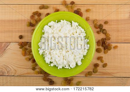 Raisins Around Green Bowl With Cottage Cheese On Wooden Table