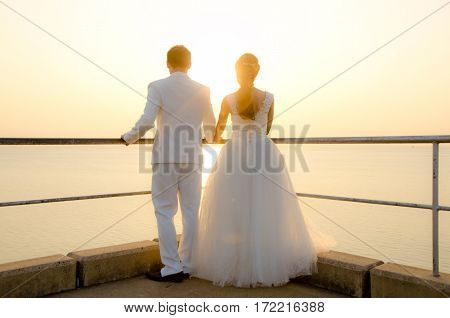 Sunset Wedding. Bride And Groom Holding Hands At Sunset .