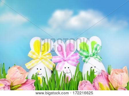 Colored easter egg bunnies on grass over blue sky background and flowers.