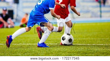 Football Match for Children. Kids Playing Soccer Tournament Game. Boys Running and Kicking Football on the Sports Field. Two Youth Soccer Players Compete for the Soccer Ball
