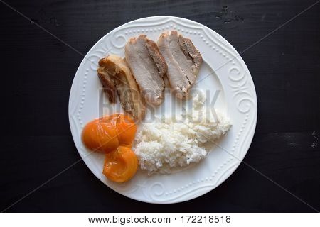 White ceramic dish of rice and roast meat, meats with apricots  on a wooden table.
