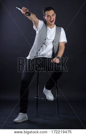 Young Male Black-haired Pop Singer Posing Singing To Microphone