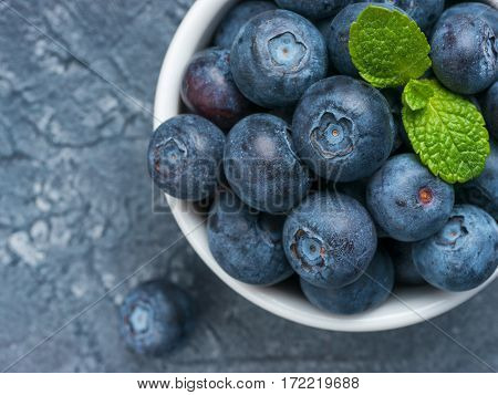 Freshly picked blueberries closeup. Ripe and juicy fresh blueberry with green mint leaves on textured concrete background. Bilberry on gray background with copyspace. Top view or flat lay