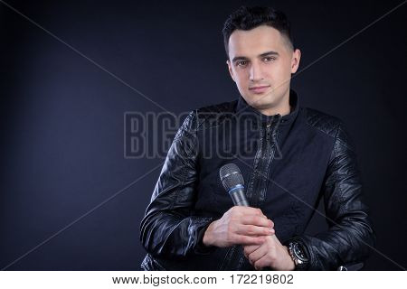 Young Male Black-haired Pop Singer Poses With Microphone