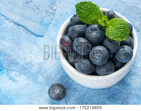 Freshly picked blueberries closeup. Ripe and juicy fresh blueberry with green mint leaves on textured concrete background. Bilberry on blue background with copyspace. Top view or flat lay