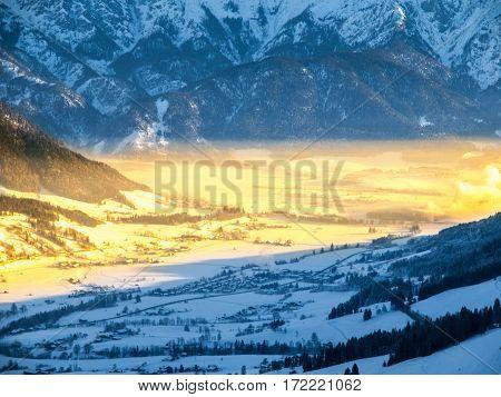 Morning in alpine valley. Winter haze illuminated by ray of rising sun, Leogang, Austria.