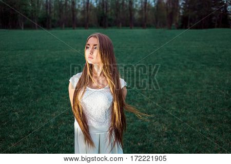 Alone Beautiful Blond Young Woman Wearing White Dress in a Mystic Evening Park. Nature Grass Copy Space.