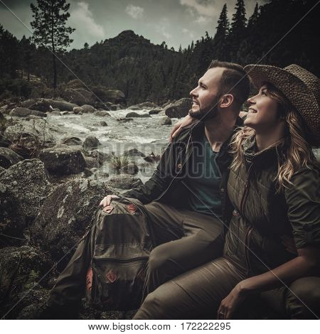 Cheerful couple hikers sitting near wild mountain river