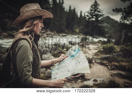 Woman hiker, searching right direction on map near wild mountain river