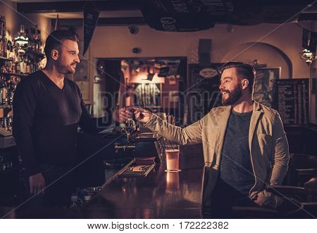 Stylish man paying for beer by card to bartender in pub