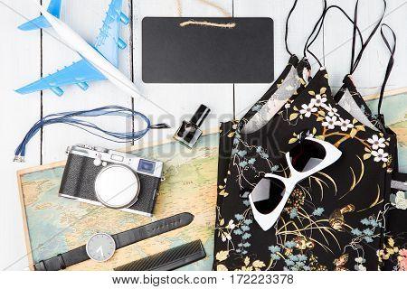 Blank Blackboard, Plane, Map, Sunglasses, Watch, Camera On White Wooden Table