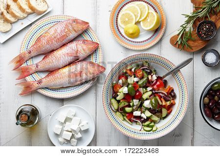 Raw mullet fish, greek salad and other mediterranean ingredients on white wooden table