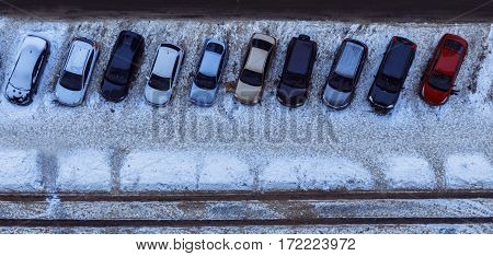 Ten cars parked near the house. The top view on parked cars. Neatly parked cars in winter