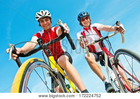Two Cyclists on racing bikes, smiling at the camera, seen from below