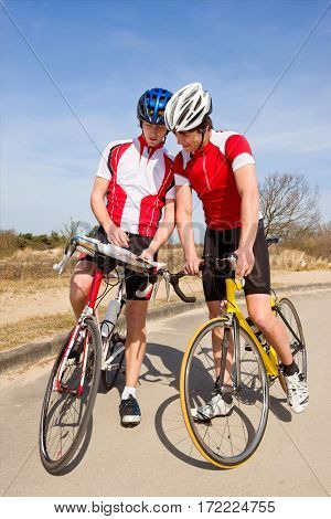 Two cyclists looking for directions on a map during a tour