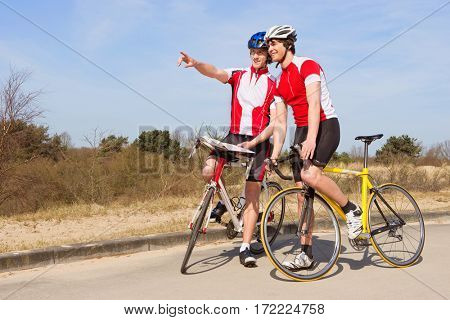 Two cyclists, standing over their bicycles looking ahead at the road to take