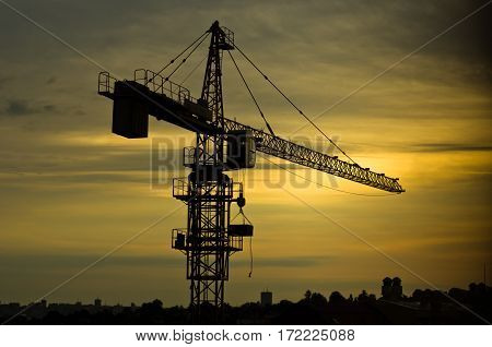 Yellow construction crane against cloudy sky at sunrise in Belgrade, Serbia