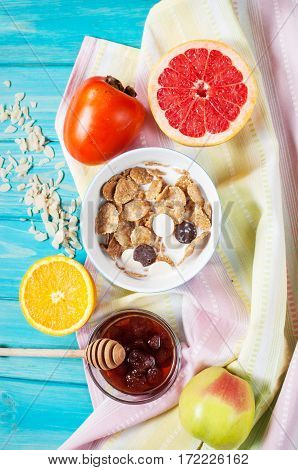Bowl of healthy corn flakes breakfast cereal with milk and fruits on blue wood table. Top view