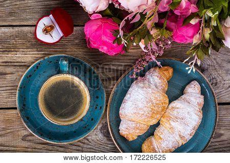 Festive breakfast of espresso, fresh croissant, flowers and gift on March 8, Birthday. Studio Photo