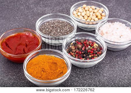 Various dry spices, sauces and cereals in glass molds on background of gray stone. Studio Photo