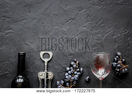 restaurant set with red wine bottle and grape on dark stone background top view mock-up