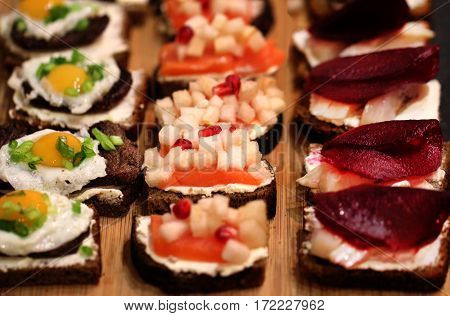 Different fresh mini sandwiches with meat and fish