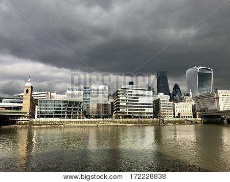 LONDON - FEBRUARY 17, 2017: Dark cloudy overcast skies over famous skyscrapers including The Gherkin and Walkie Talkie in the financial district of the City of London near London Bridge in London, UK.