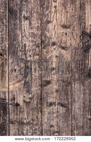 The surface of the old door. On the surface are many dents scratches and nails.